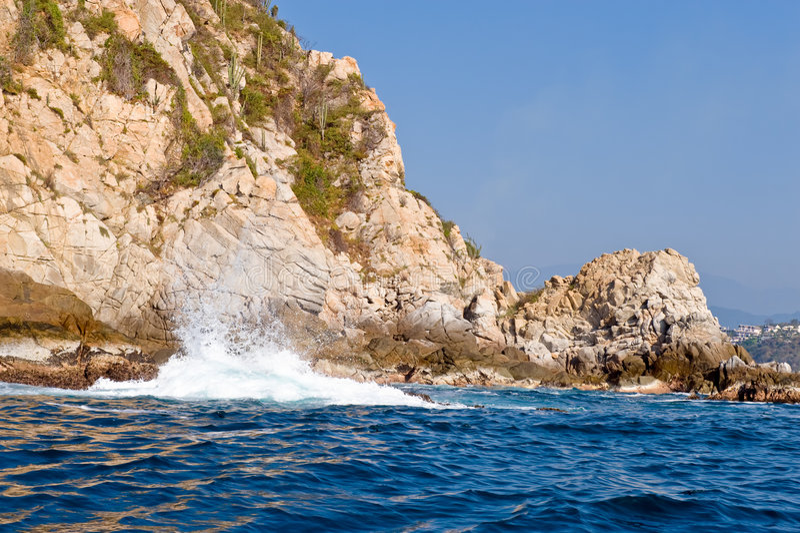 Huatulco Mexico coast. A view of waves of the Pacific Ocean crashing on the shoreline of Huatulco, Mexico stock photos