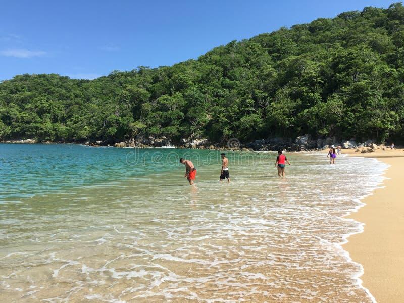 Huatulco, Oaxaca Jovens que jogam na praia imagens de stock royalty free