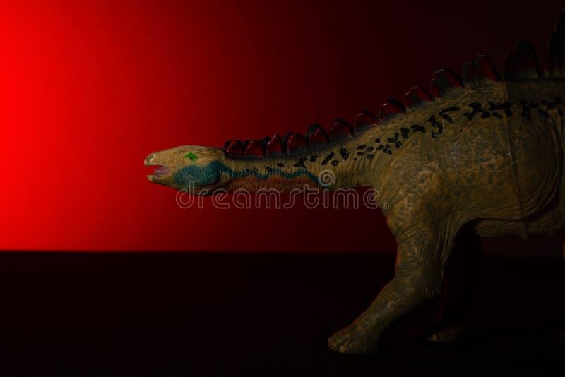 Huayangosaurus med fläckljus på huvudet och röda ljuset på bakgrund arkivbilder
