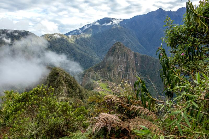 Huayna Picchu, ou Wayna Pikchu, montanha nas nuvens aumentam sobre a citadela do Inca de Machu Picchu, perderam a cidade dos Inca foto de stock