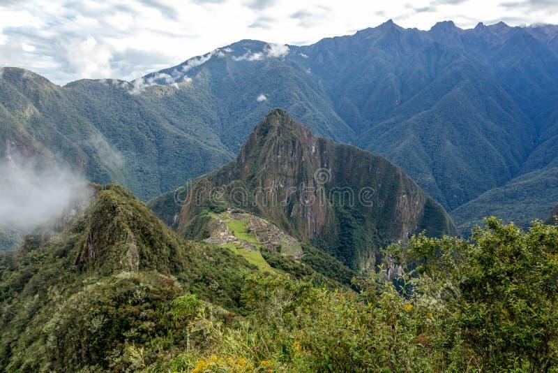 Huayna Picchu, or Wayna Pikchu, mountain in clouds rises over Machu Picchu Inca citadel, lost city of the Incas. Background with Huayna Picchu, Wayna Pikchu stock photography