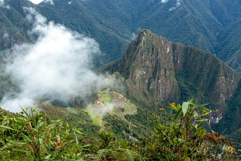 Huayna Picchu, or Wayna Pikchu, mountain in clouds rises over Machu Picchu Inca citadel, lost city of the Incas stock photography