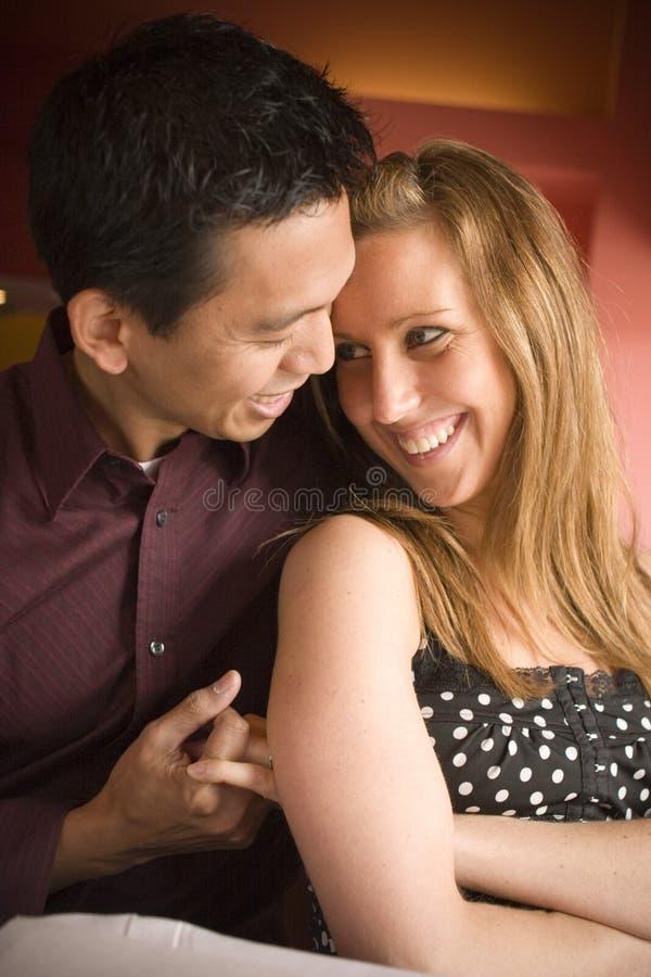 hubbing在咖啡馆的多种族夫妇 免版税库存图片