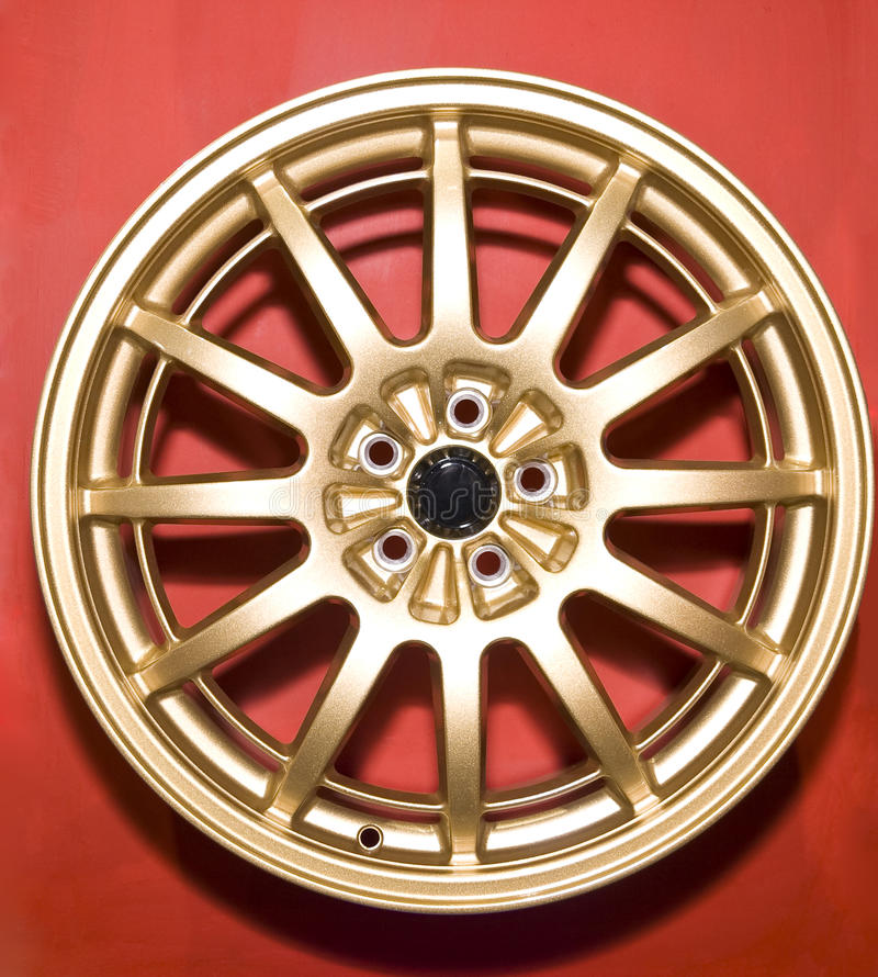 Hubcap. A golden hubcap isolated over red background stock photo