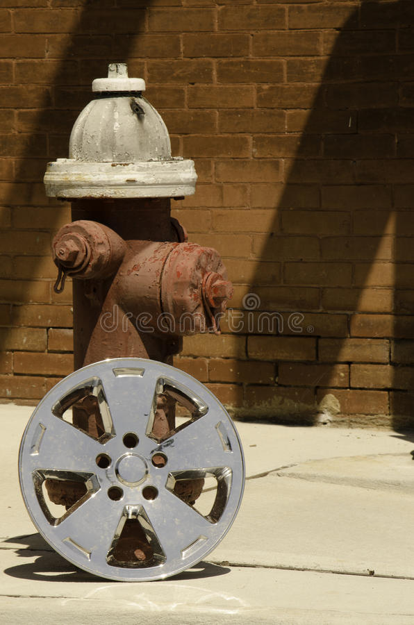 Hubcap & Hydrant. A hubcap rests against a fire hydrant in the midday sun royalty free stock photo