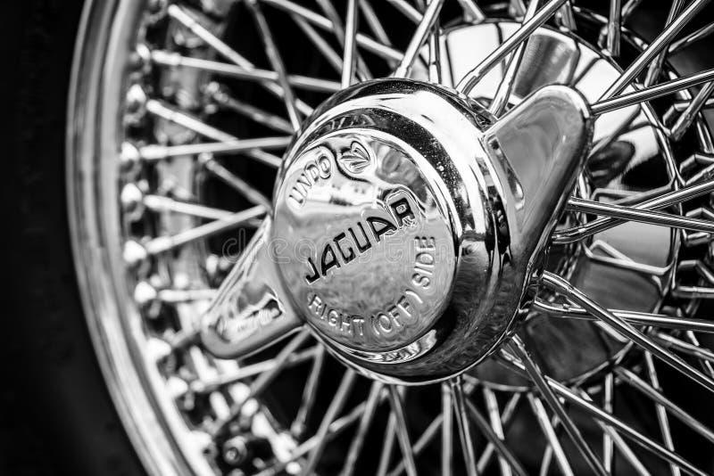 Hubcap of sports car Jaguar E-Type, closeup. PAAREN IM GLIEN, GERMANY - JUNE 03, 2017: Hubcap of sports car Jaguar E-Type, closeup. Black and white. Exhibition royalty free stock photography