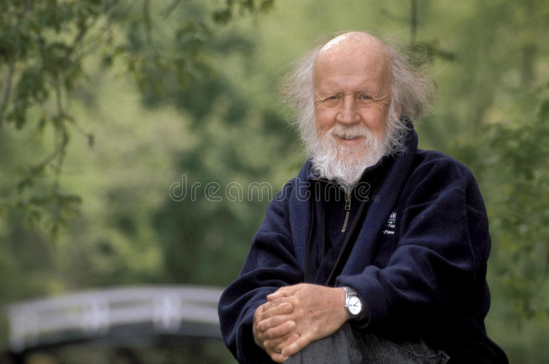Hubert Reeves. Portrait of hubert reeves, the famous astrophysician author of numerous book, he is sitting in a smiling attitude, in front of a pond surrounded stock photo