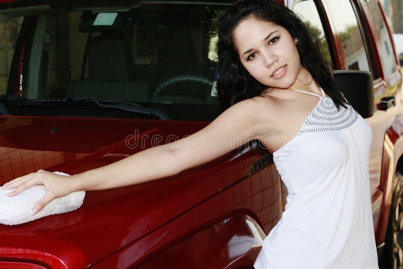 Hublot de véhicule de lavage de jeune femme avec l'éponge images stock