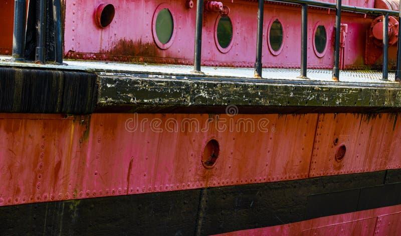 Hublots et plate-forme sur un vieux bateau rouillé rouge image libre de droits