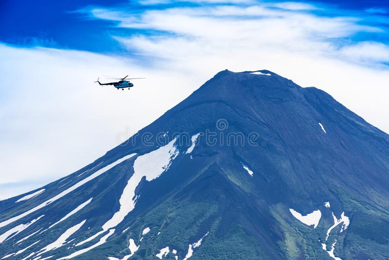 Hubschrauber, der über Ilyinsky-Vulkan und Kurile See fliegt stockbilder