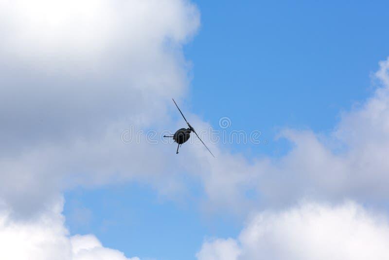 Hubschrauber, der gegen einen blauen Himmel mit Wolken schwebt lizenzfreies stockfoto
