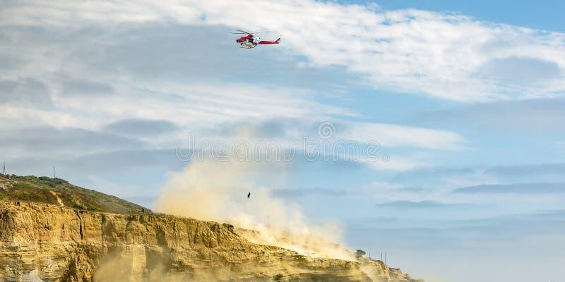 Hubschrauber im Flug auf bewölktem Himmel über einer Klippe stockfotos