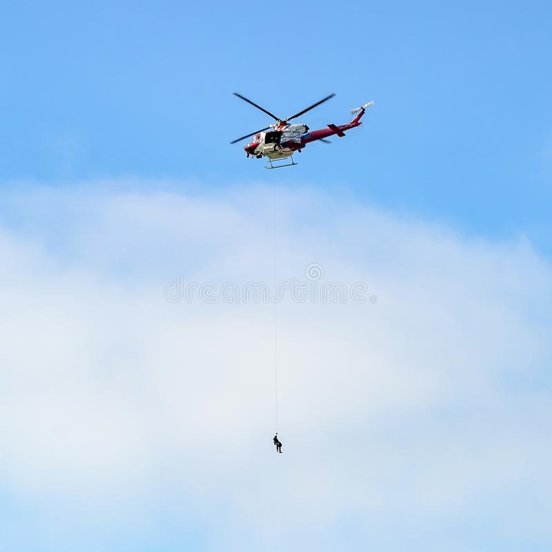 Hubschrauber mit der Person, die vorbei hängt, fangen La Jolla ein stockfotos