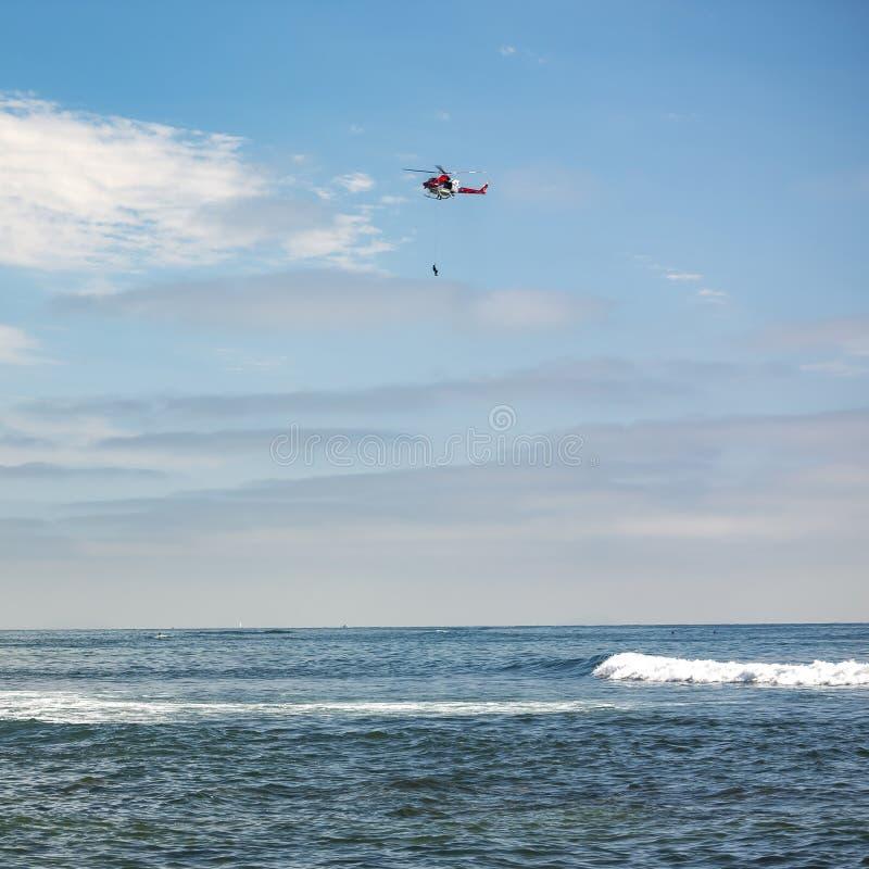 Hubschrauber mit hängender Person über La- Jollameer stockfotos