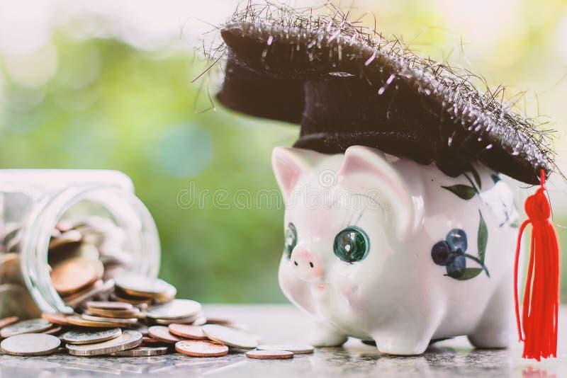 Hucha con el casquillo académico cuadrado y el tarro de cristal de monedas imagen de archivo libre de regalías