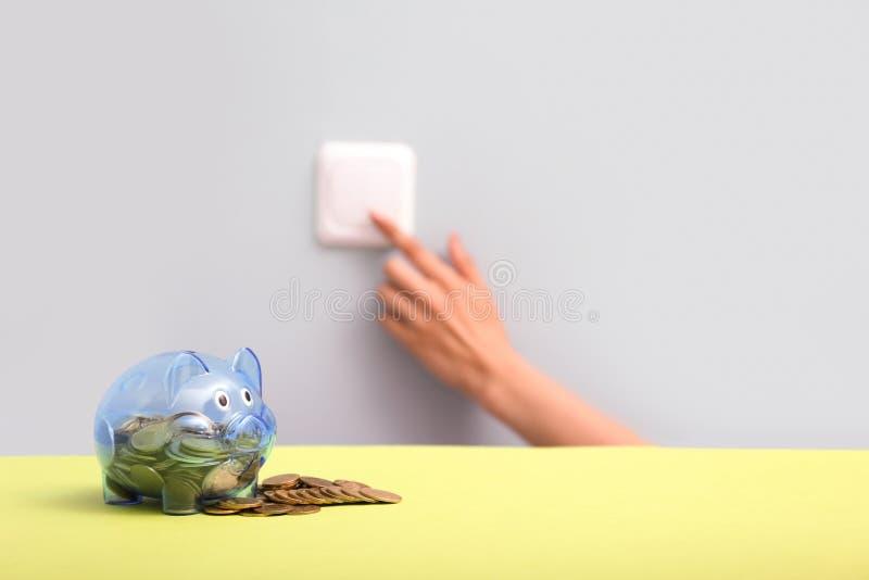 Hucha con las monedas y la mano femenina que encienden la luz usando el interruptor en la pared Concepto del ahorro de la electri imagen de archivo libre de regalías