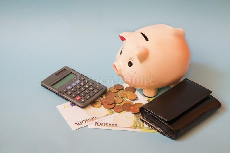 Hucha con los billetes de banco y las monedas euro, monedero y calculadora en fondo azul fotos de archivo