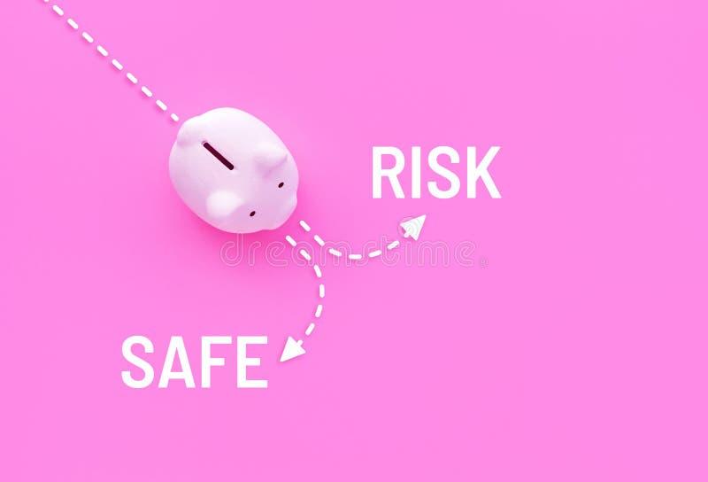 Hucha con riesgo y texto seguro en fondo rosado del color en colores pastel foto de archivo