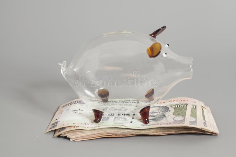 Hucha de cristal con los billetes de banco indios de la rupia de la moneda imágenes de archivo libres de regalías