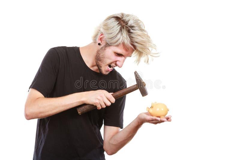 Hucha de la rotura del hombre de Sreaming que intenta con el martillo fotografía de archivo libre de regalías