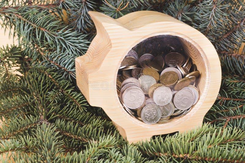 Hucha de madera amarilla con las monedas de las rublos rusas Fondo de la Navidad y del A?o Nuevo con las ramas de la picea Taller fotografía de archivo libre de regalías