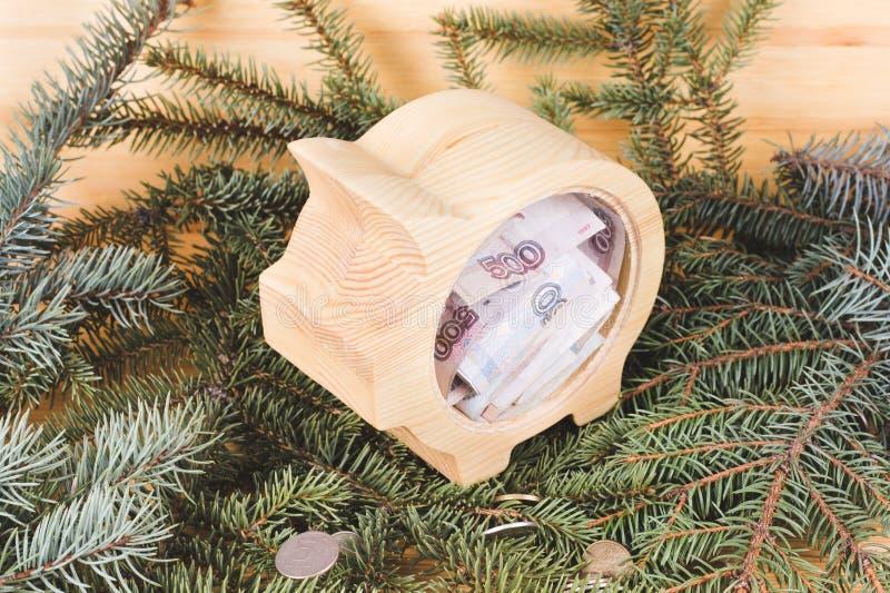 Hucha de madera amarilla con los billetes de banco de la rublo rusa Fondo de la Navidad y del A?o Nuevo con las ramas de la picea fotos de archivo