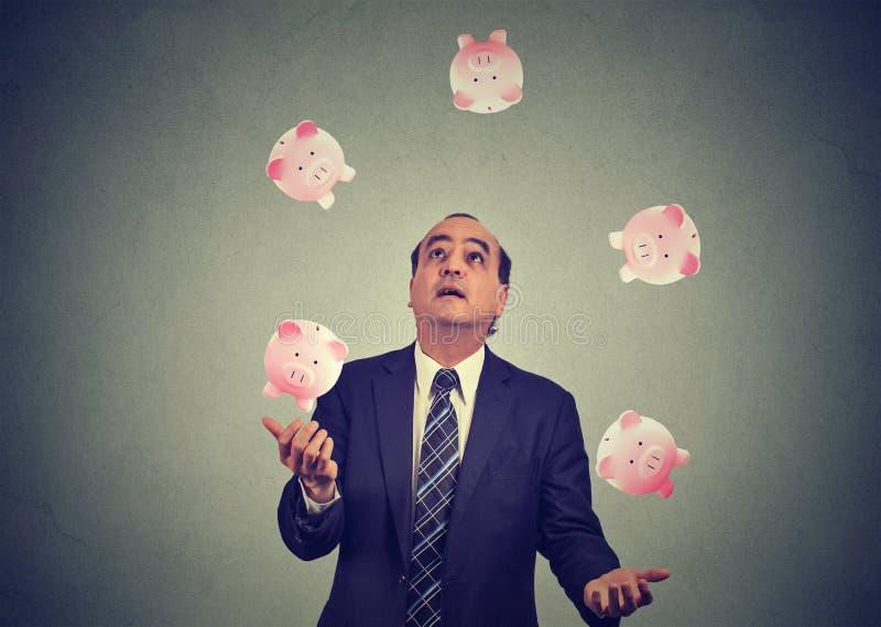 Hucha del dinero del hombre de negocios que hace juegos malabares imagenes de archivo