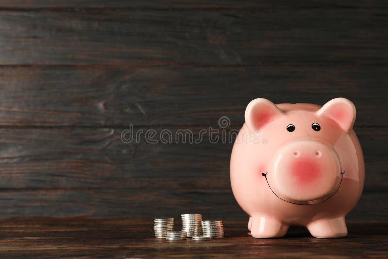 Hucha feliz con el dinero en la tabla de madera contra el fondo de madera, espacio para el texto fotografía de archivo libre de regalías