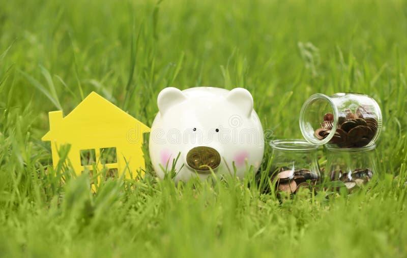 Hucha, figura de la casa y tarros con las monedas en hierba verde foto de archivo