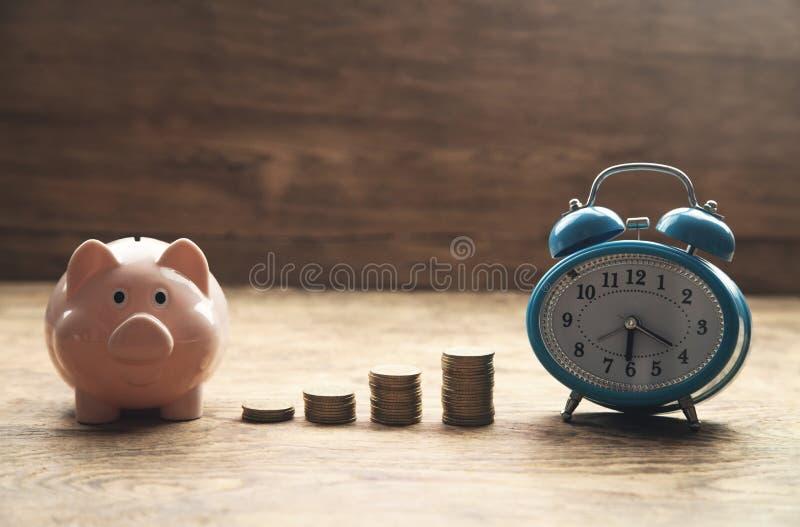 Hucha, pila de monedas y despertador en la tabla de madera Tiempo fotografía de archivo