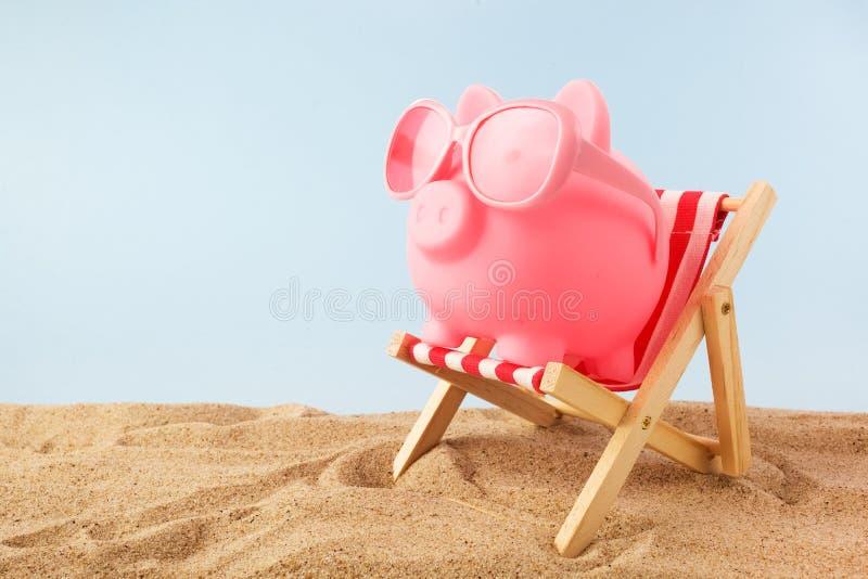 Hucha rosada con las gafas de sol en la silla de cubierta en la playa fotografía de archivo libre de regalías
