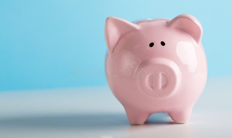 Hucha rosada para los ahorros de las monedas en fondo azul imagen de archivo