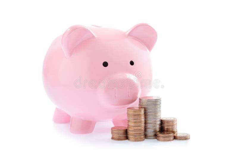 Hucha y pilas rosadas de monedas del dinero foto de archivo libre de regalías