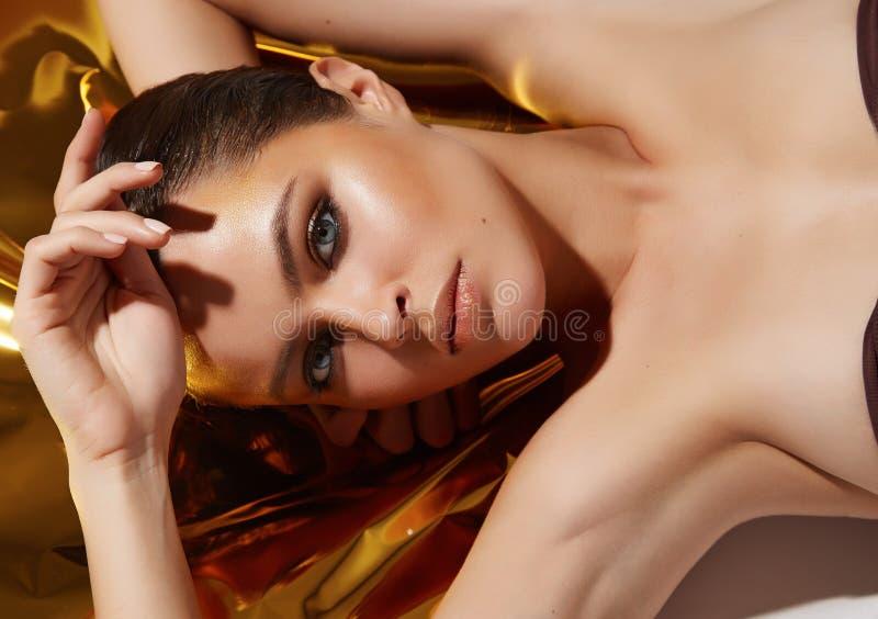 Hud för skönhet för härligt sexigt kvinnasmink guld- solbränd royaltyfria bilder