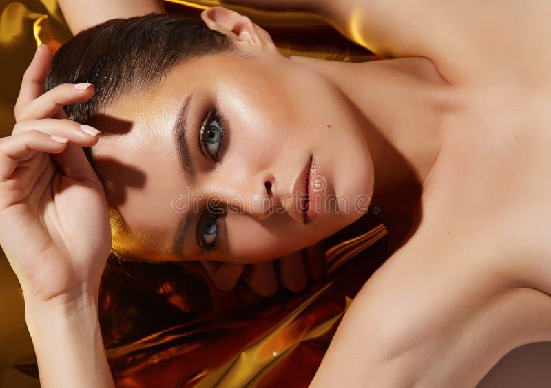 Hud för skönhet för härligt sexigt kvinnasmink guld- solbränd arkivfoto