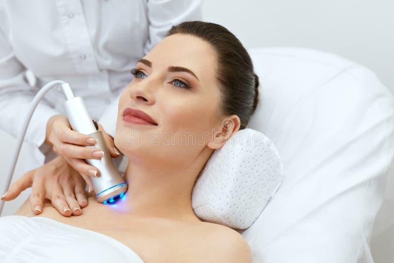 HudCosmetology Kvinna som gör blå ljus terapi på hals arkivbilder