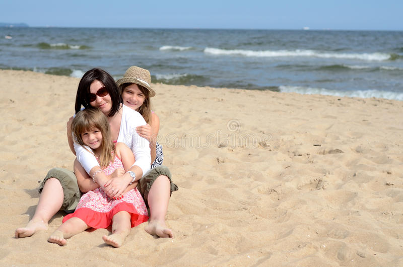 Download Huddled Girls On The Sunny Beach Stock Photo - Image of female, expression: 21363234