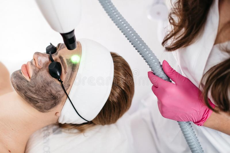 Hudomsorg och skönhetsmedel Skönhetlaser-behandling Kvinna och hälsa Klienten mottar framsidalaser-behandlingen in royaltyfri bild