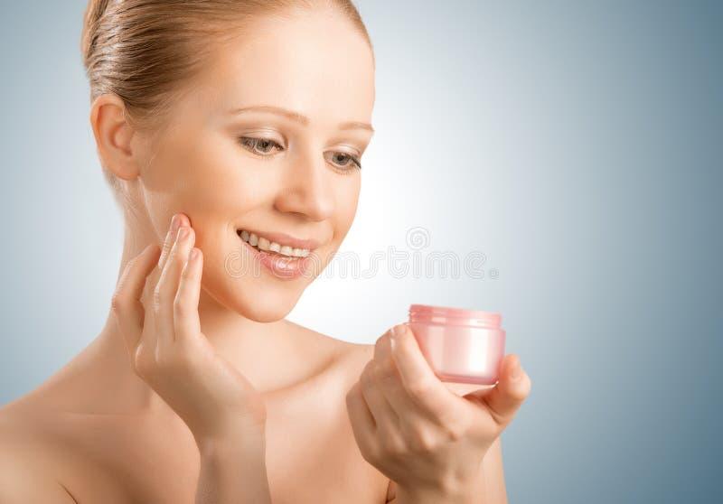 Hudomsorg.  skönhetkvinnan med ögon stängde sig med kruset av kräm arkivfoton