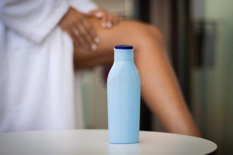Hudomsorg under sommarbegrepp: närbild en flaska av kräm och kvinnan som applicerar kropplotion på henne ben arkivfoto