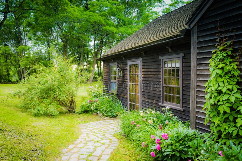 Hudson Valley Country Cottage Entry. A wood cottage surrounded by perennial borders and tall trees in Upstate New York royalty free stock photos