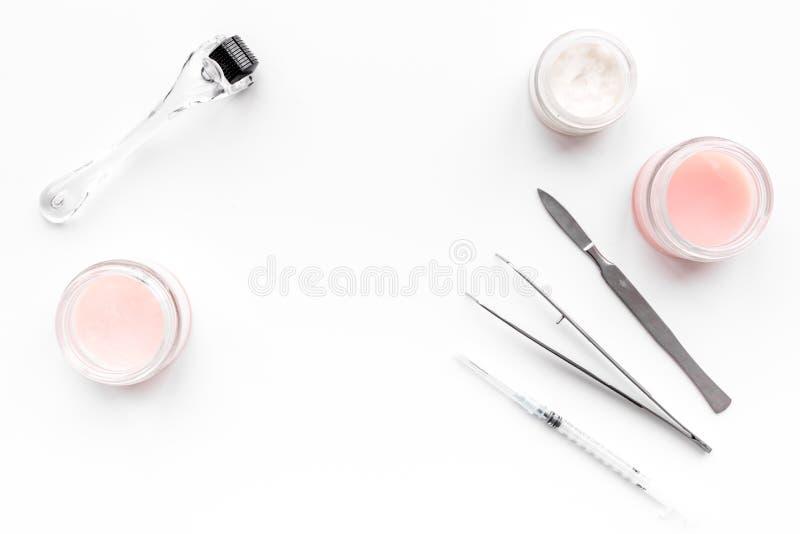 Hudspecialist- eller cosmetologisttillbehör Dermaroller, krämer och maskering, skönhetinjektion, hjälpmedel på vit bakgrund fotografering för bildbyråer