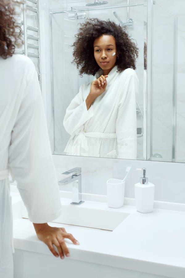 Hudvård Kräv för kvinnor som ansöker i ansiktet och som tittar i badrumsspegeln royaltyfri fotografi