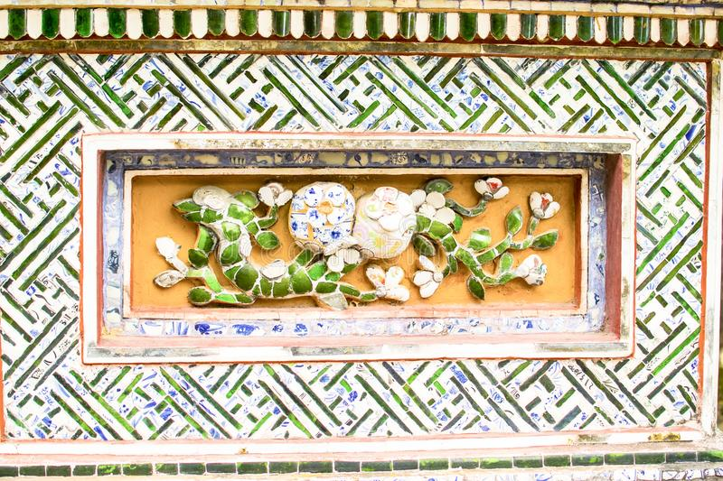 HUE, VIETNAM, April 28th, 2018: Fragment of an old wall with an ancient decorative element. Vietnam.  stock photos