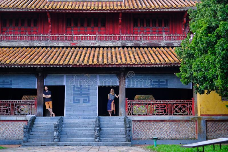 Hue / Vietnam, 17/11/2017: Couple standing inside a traditional house with ornamental tiled roof in the Citadel of Hue, Vietnam stock photography