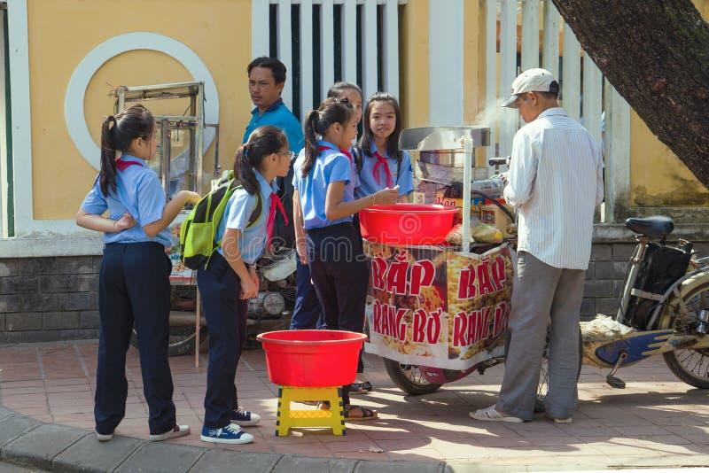 Vietnamese schoolgirls buy popcorn from a street vendor. HUE, VIETNAM - JANUARY 08, 2016: Vietnamese schoolgirls buy popcorn from a street vendor stock image