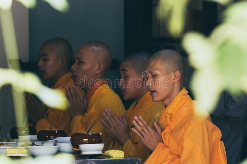 Hue, Vietnam - June 2019: Buddhist monks saying traditional prayer chants before meal in Thien Mu Pagoda stock photo