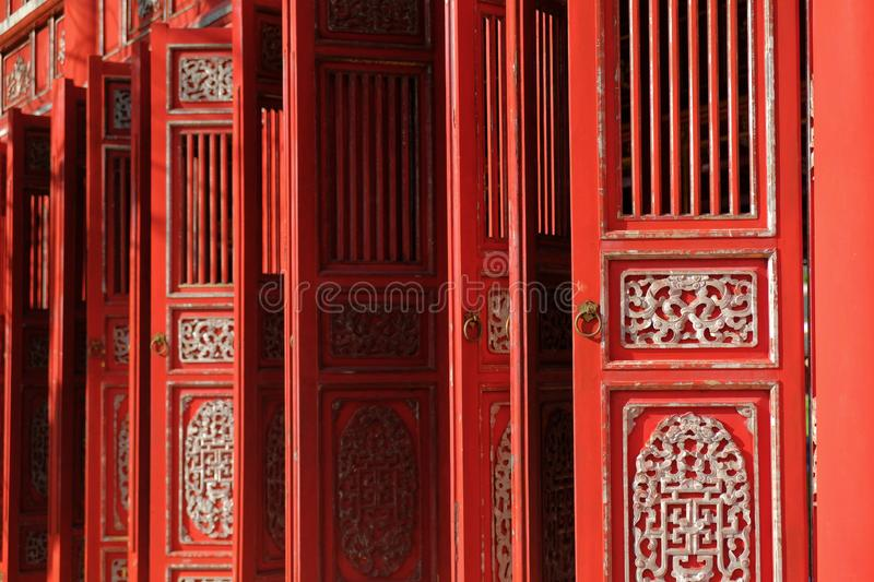 Hue / Vietnam, 17/11/2017: Red ornamental doors in a traditional pavillion in the Citadel complex in Hue, Vietnam royalty free stock image