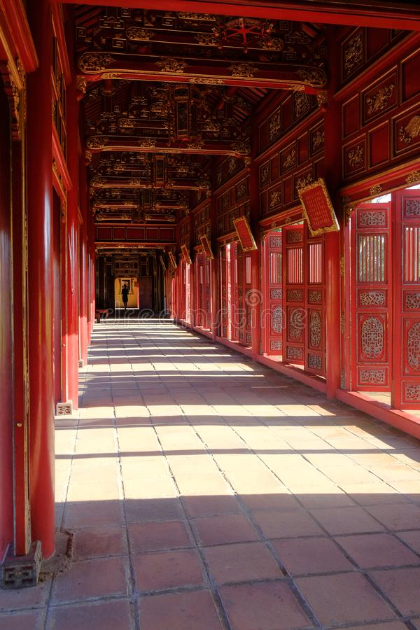 Hue / Vietnam, 17/11/2017: Woman passing through a red ornamental pavillion in the Citadel complex in Hue, Vietnam royalty free stock images