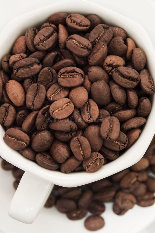 Granos de café en la taza y la placa blancas fotografía de archivo